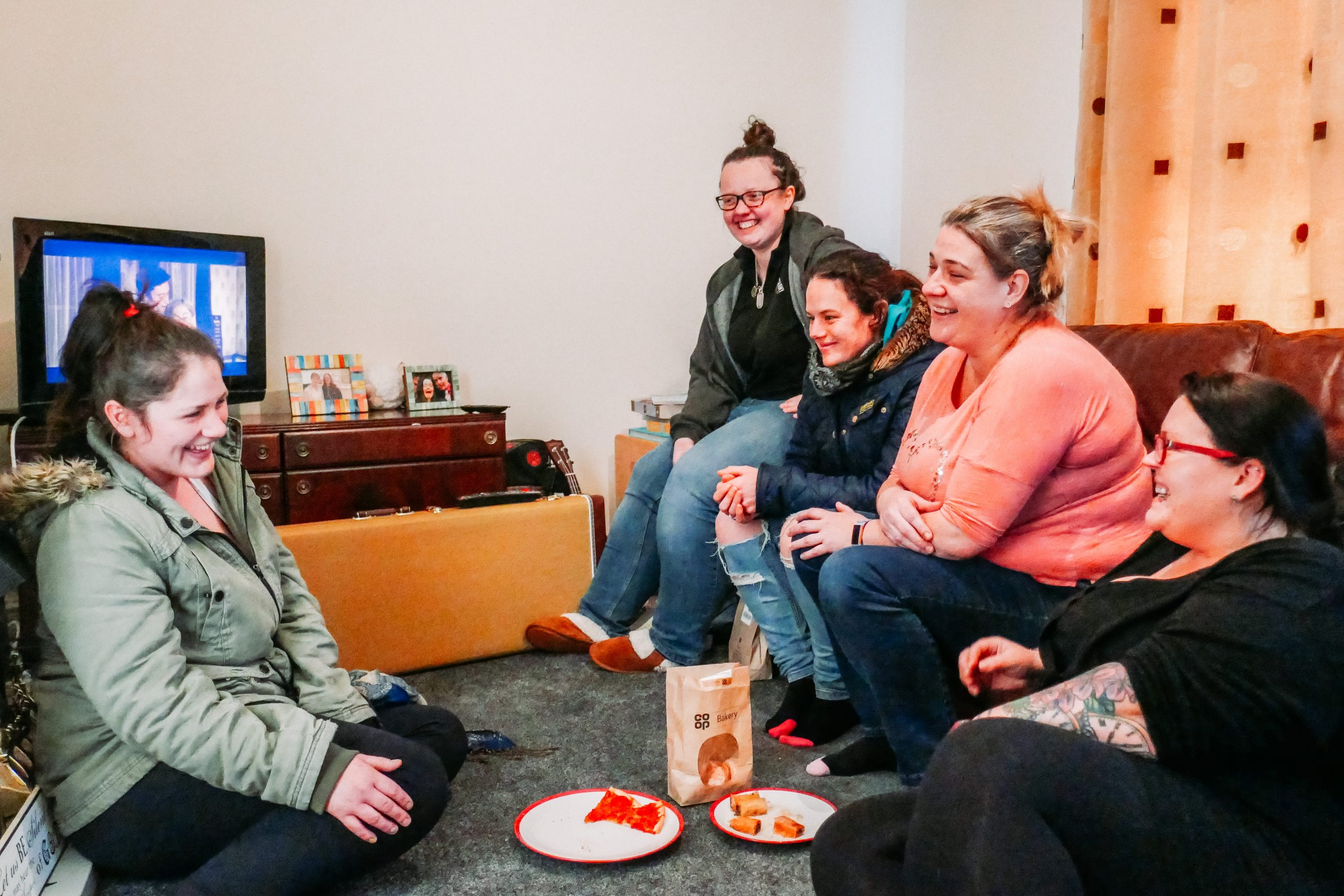 Amy and other women in a living room laughing and eating biscuits